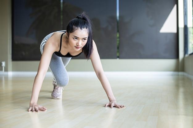 Jonge vrouwen worden opgewarmd voordat ze gaan sporten door de vloer te duwen en zijn knieën in de sportschool te buigen.
