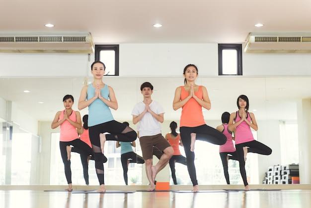Jonge vrouwen yoga binnen blijven kalm en mediteren terwijl u yoga oefent om de innerlijke vrede te verkennen. yoga en meditatie hebben goede voordelen voor de gezondheid. foto concept voor yoga sport en gezonde levensstijl