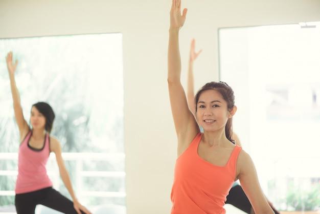 Jonge vrouwen yoga binnen blijven kalm en mediteren terwijl yoga oefent om de innerlijke vrede te verkennen. yoga en meditatie hebben goede voordelen voor de gezondheid. foto concept voor yoga sport en gezonde levensstijl