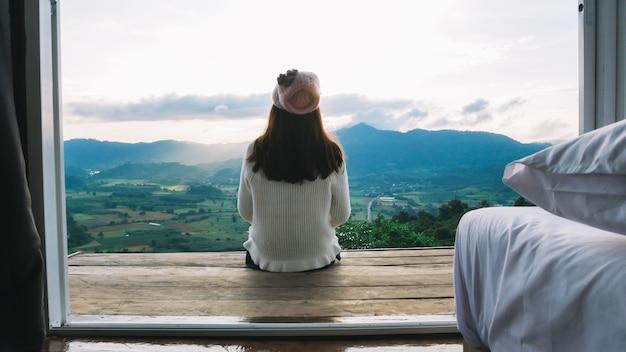 Jonge vrouwen zaten op een houten vloer en genoten 's ochtends van het uitzicht op de bergen.