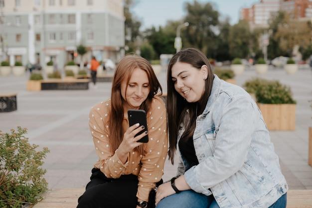 Jonge vrouwen zitten in een stadspark met een telefoon