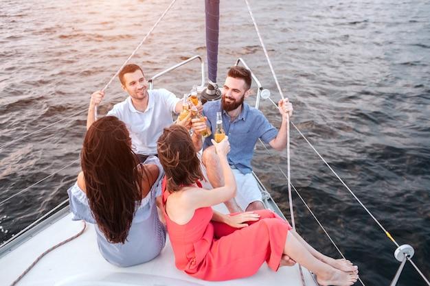 Jonge vrouwen zitten oog in oog met mannen. ze bevatten allemaal flessen met bier. zij vieren. man aan de linkerkant houden touw met de hand. de man rechts doet hetzelfde.