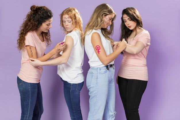 Jonge vrouwenactivisten die schilderen voor protest