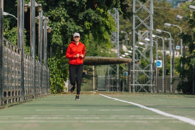 Jonge vrouwenagent op straat loopt voor oefening op stadsweg; concept van sport, mensen, sporten en levensstijl