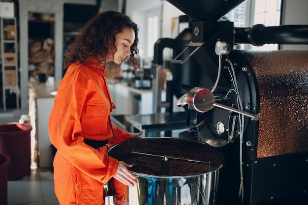 Jonge vrouwenarbeider in oranje kostuum in workshop met koffiebrandermachine tijdens koffiebrandproces