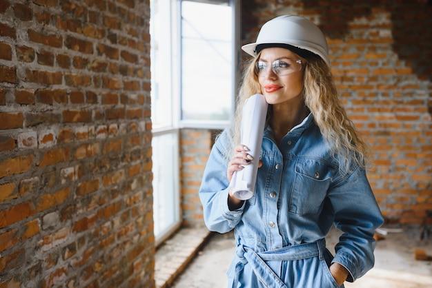 Jonge vrouwenarbeider met een witte helm op de bouwplaats.