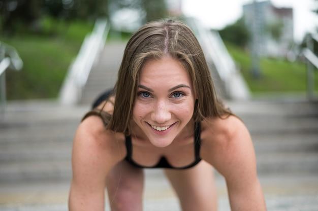 Jonge vrouwenatleet bij startpositie klaar te beginnen