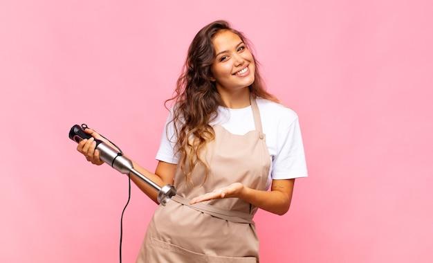 Jonge vrouwenbakker die vrolijk glimlacht, zich gelukkig voelt en een concept in exemplaarruimte met handpalm toont