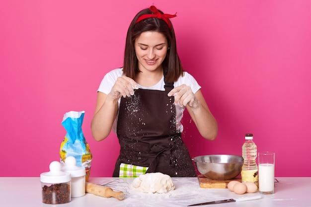 Jonge vrouwenbakker in keuken, die witte bloem op deeg bestrooit, heerlijke coockies bakt, houdt van eigengemaakt gebakje, stellen geïsoleerd op roze. kopieer ruimte voor uw advertentie of promotie.