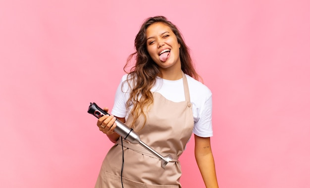 Jonge vrouwenbakker met vrolijke, zorgeloze, rebelse houding, grappen maken en tong uitsteken, plezier maken