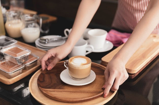 Jonge vrouwenbarista die zich bij van de de holdingskop van de koffiewinkel verse hete latte van de kop de dienende orde bij koffiewinkel bevinden.