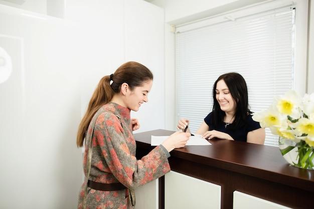 Jonge vrouwenbeheerder in een tandkliniek op het werk. toelating van de cliënt