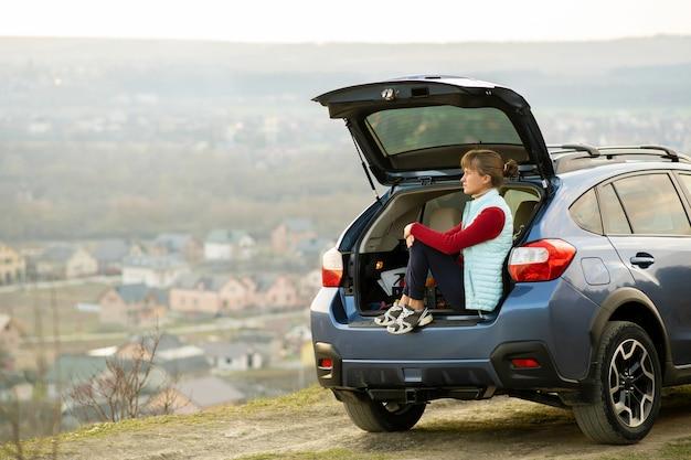 Jonge vrouwenbestuurder die alleen in haar auto zit die van mening van aardlandschap geniet.