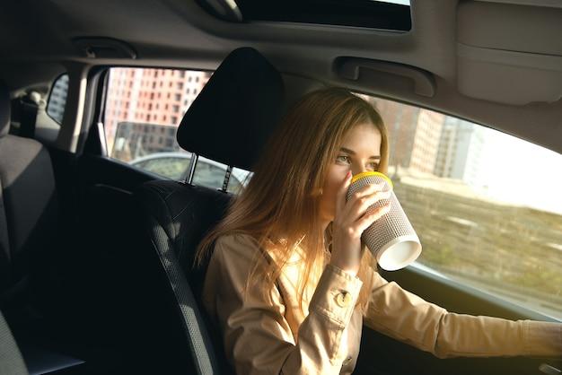 Jonge vrouwenbestuurder die een kop hete koffie in bewegende auto drinken.