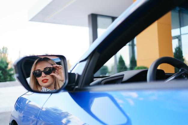 Jonge vrouwenbestuurder die in de zijspiegel van de auto kijkt en ervoor zorgt dat de lijn vrij is voordat hij een bocht maakt.