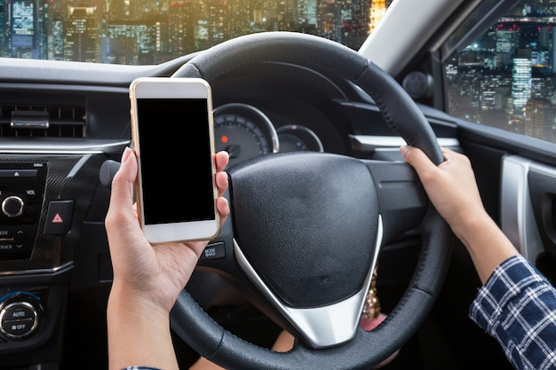 Jonge vrouwenbestuurder die smartphone van het aanrakingsscherm en het stuurwiel van de handholding in een auto gebruiken