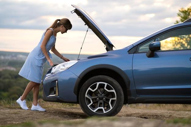 Jonge vrouwenbestuurder die zich dichtbij een kapotte auto met open kap bevindt die problemen met haar voertuig heeft