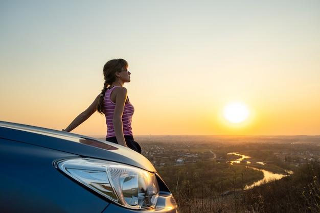Jonge vrouwenbestuurder die zich dichtbij haar auto bevindt die van warme zonsondergangmening geniet. meisjesreiziger die op voertuigkap leunen die avondhorizon bekijken.