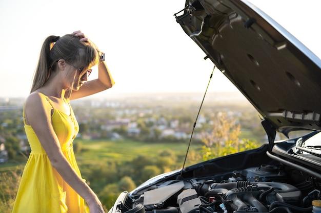 Jonge vrouwenbestuurder die zich dichtbij haar auto met open kap bevindt die motorprobleem heeft.