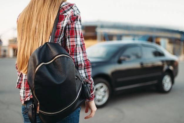 Jonge vrouwenbestuurder met zak tegen een auto