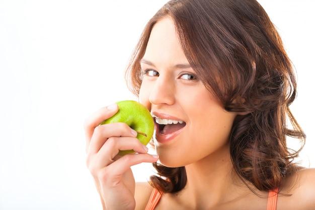 Jonge vrouwenbeten in een verse en gezonde appel