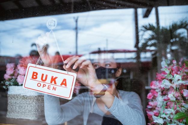 Jonge vrouwenbloemist die een schort en een gezichtsmasker draagt die zich bij het venster van een bloemenemmer bevindt die een open tekstteken in het venster geeft