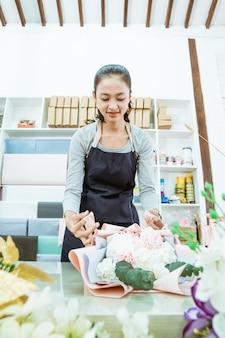 Jonge vrouwenbloemist die in bloemenwinkel werken die de bloem van het ordeflanel in een lijstwerkruimte voorbereiden