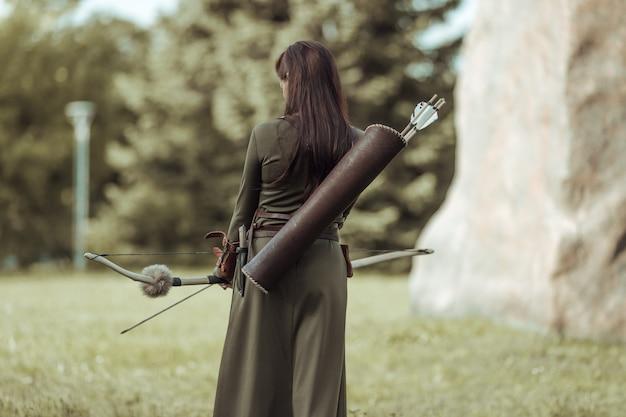 Jonge vrouwenboogschutter in groen middeleeuws kostuum