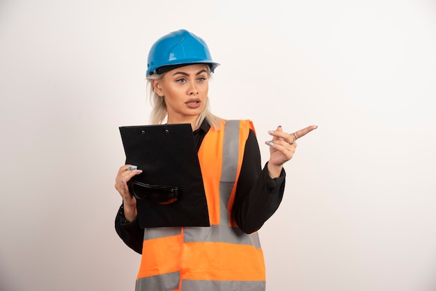 Jonge vrouwenbouwer die met klembord ergens richt. hoge kwaliteit foto