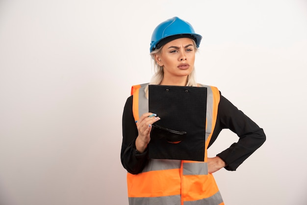 Jonge vrouwenbouwer die weg met klembord kijkt. hoge kwaliteit foto