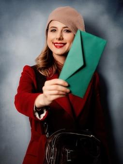 Jonge vrouwenbrievenbesteller met groene envelop