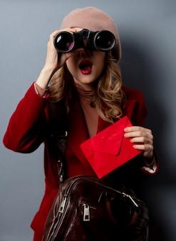 Jonge vrouwenbrievenbesteller met rode envelop en verrekijker