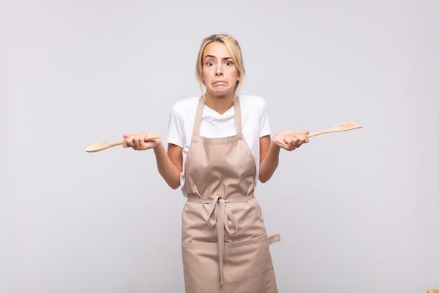 Jonge vrouwenchef die zich in verwarring en verward voelt, twijfelt, weegt of verschillende opties kiest met grappige uitdrukking