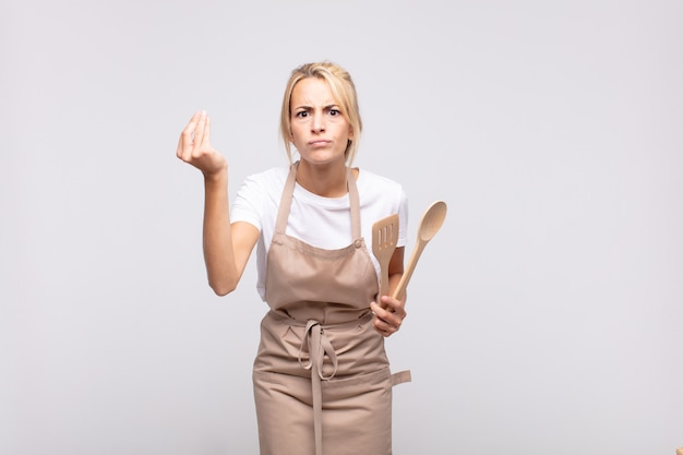 Jonge vrouwenchef-kok die capice of geldgebaar maakt, die u vertelt uw schulden te betalen!