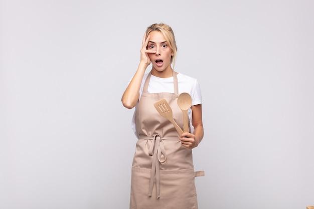 Jonge vrouwenchef-kok die geschokt, bang of doodsbang kijkt, gezicht bedekt met hand en tussen vingers gluurt