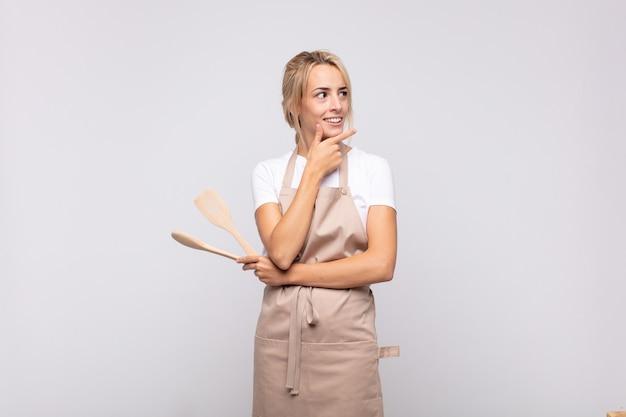 Jonge vrouwenchef-kok die met een gelukkige, zekere uitdrukking met hand op kin glimlacht, zich afvraagt en naar de kant kijkt
