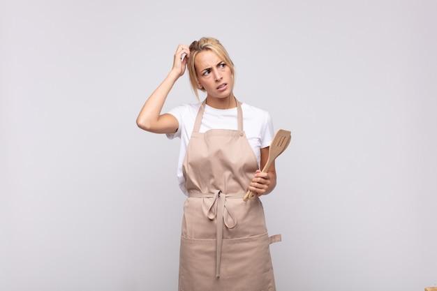 Jonge vrouwenchef-kok die zich in verwarring en verward voelt, hoofd krabt en naar de kant kijkt