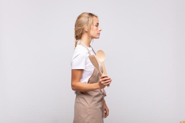 Jonge vrouwenchef-kok op profielweergave die ruimte vooruit willen kopiëren, denken, verbeelden of dagdromen