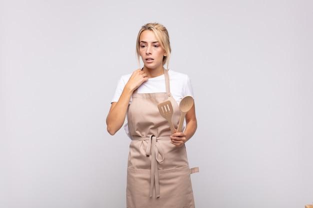 Jonge vrouwenchef-kok voelt zich gestrest, angstig, moe en gefrustreerd, trekt de hals van het shirt aan en kijkt gefrustreerd door het probleem