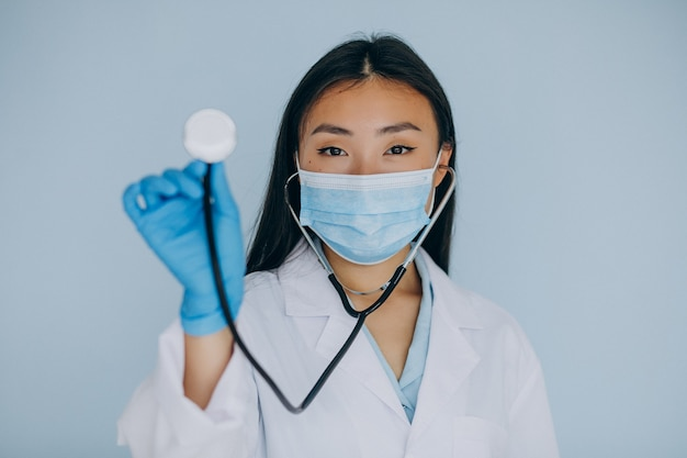 Jonge vrouwenchirurg op blauwe achtergrond met stethoscope