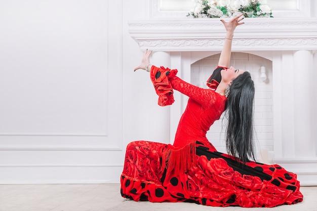Jonge vrouwendanser in rode kleding die zigeunerdans uitvoert