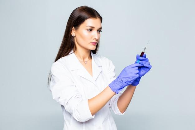 Jonge vrouwendokter met een spuit in haar hand op witte muur.