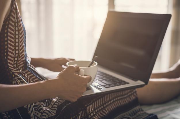 Jonge vrouwendrank van koffie en het gebruiken van laptop computer