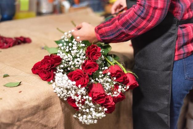 Jonge vrouweneigenaar die van bloemistwinkel boeket van rozen schikken.