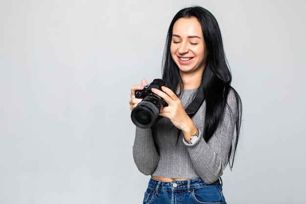 Jonge vrouwenfotograaf die met camera schieten die op grijze muur wordt geïsoleerd