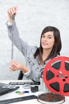 Jonge vrouwenfotograaf die negatieve film bekijken
