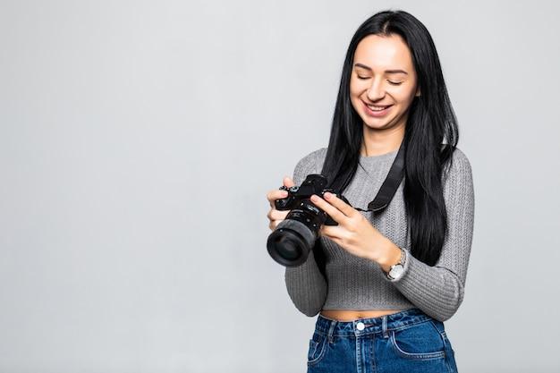 Jonge vrouwenfotograaf met camera die op grijze muur wordt geïsoleerd