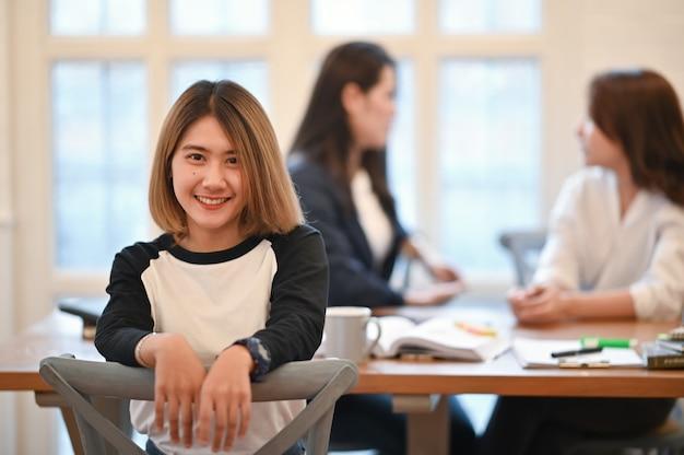 Jonge vrouwenglimlach op gezicht met portret dat in campusbibliotheek is ontsproten.