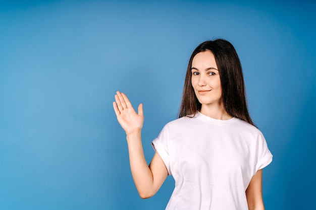 Jonge vrouwengroet met hand die op blauwe muur wordt geïsoleerd