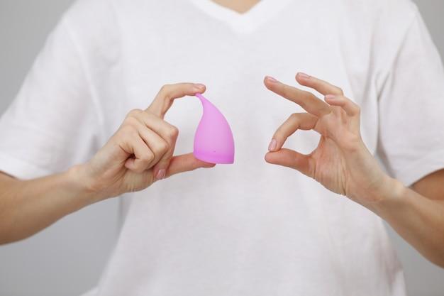 Jonge vrouwenhand die menstruele kop houdt. vrouwengezondheidsconcept, geen afvalverspilling. ok teken vingers.